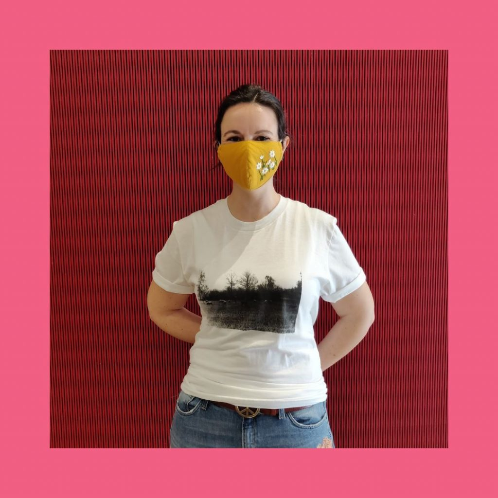 A young woman in a face mask models a white T-Shirt featuring the visual art piece The Wild Ones and The Colonized by Shelley Niro.