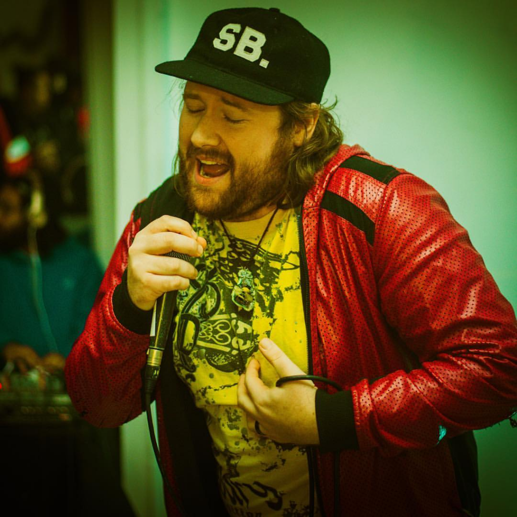 London hip hop artist Strange Breed performing into a microphone