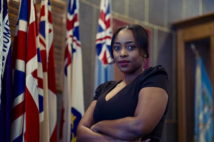London City Councillor Arielle Kayabaga stands, arms folded in front of Canada's provincial flags.