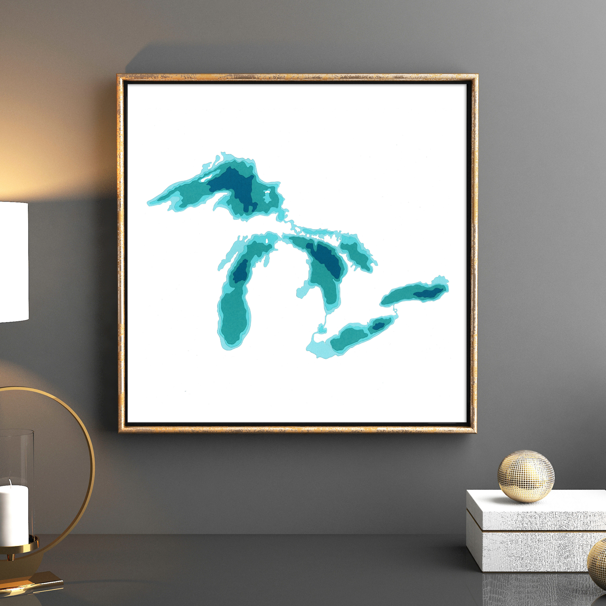 A framed image of the five great lakes in teal and dark blue. the background is white. the frame is gold. Cardtography.