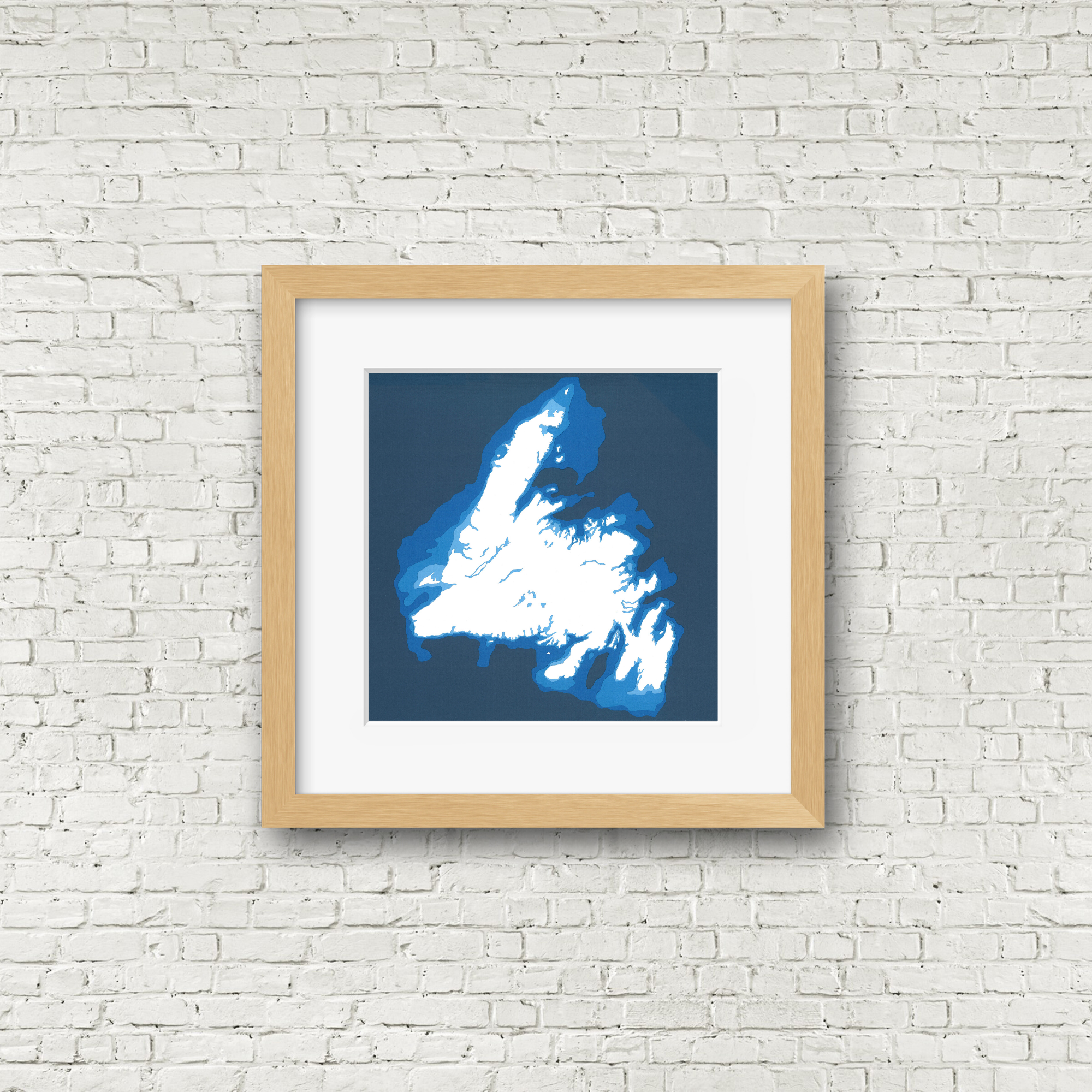 A framed image of Newfoundland where the island is white and the water is blue. The frame hangs on a white brick wall. Cardtography designs.