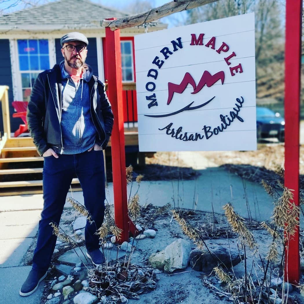 """A man in a jacket stands with his hands in his pockets next to a sign that says """"Modern Maple Artisan Boutique."""" these is a small house behind him."""