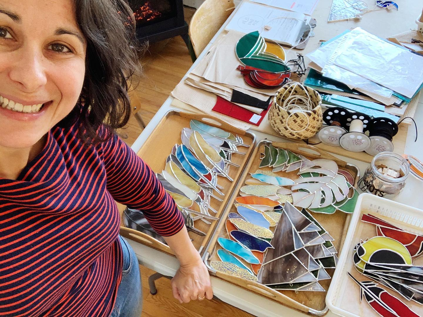 A woman poses a for a selfie smiling with stained glass pieces next to her.