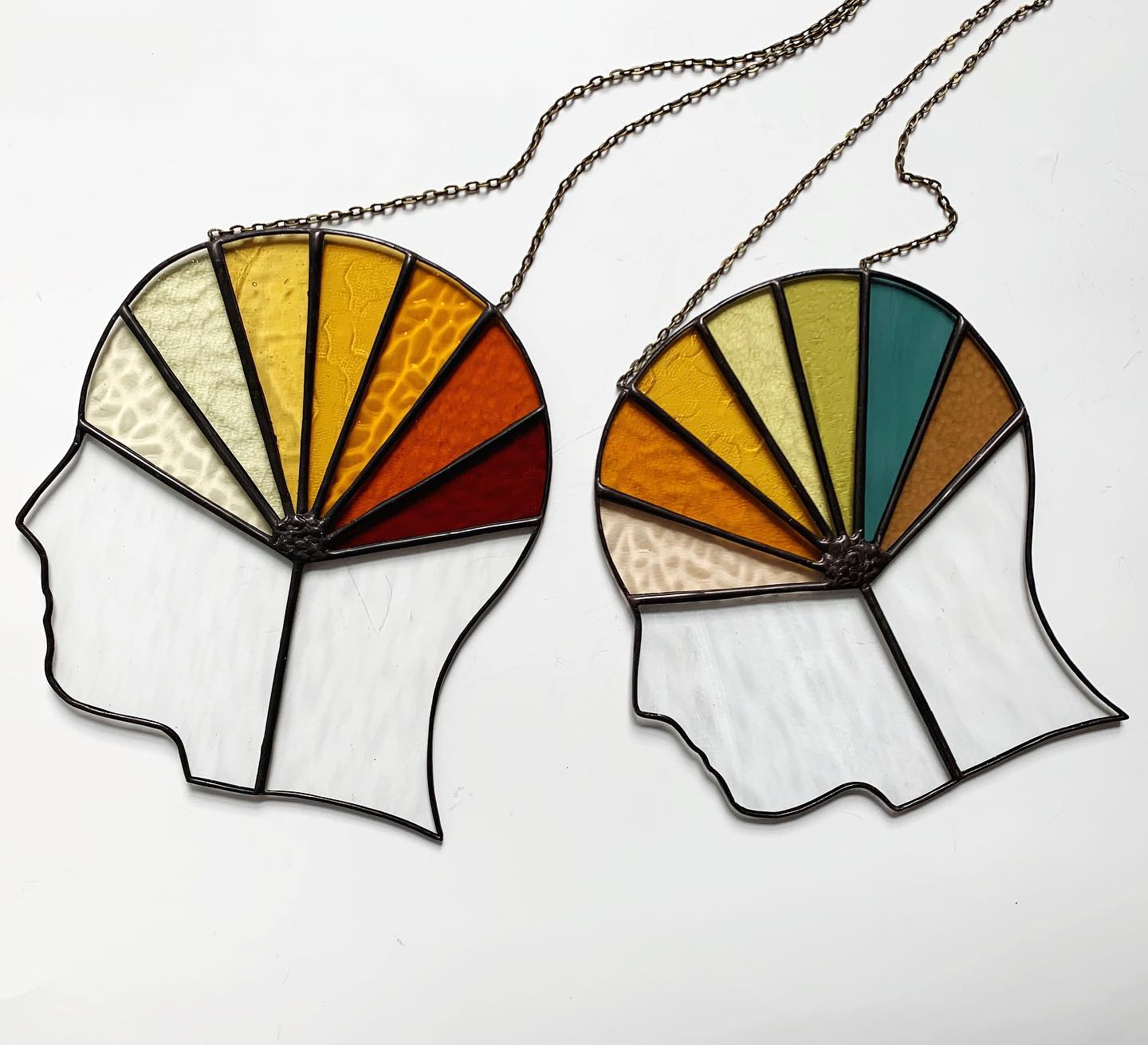 Two stained glass pieces silhouettes with vibrant colours in the brain from Forest City Stained Glass.