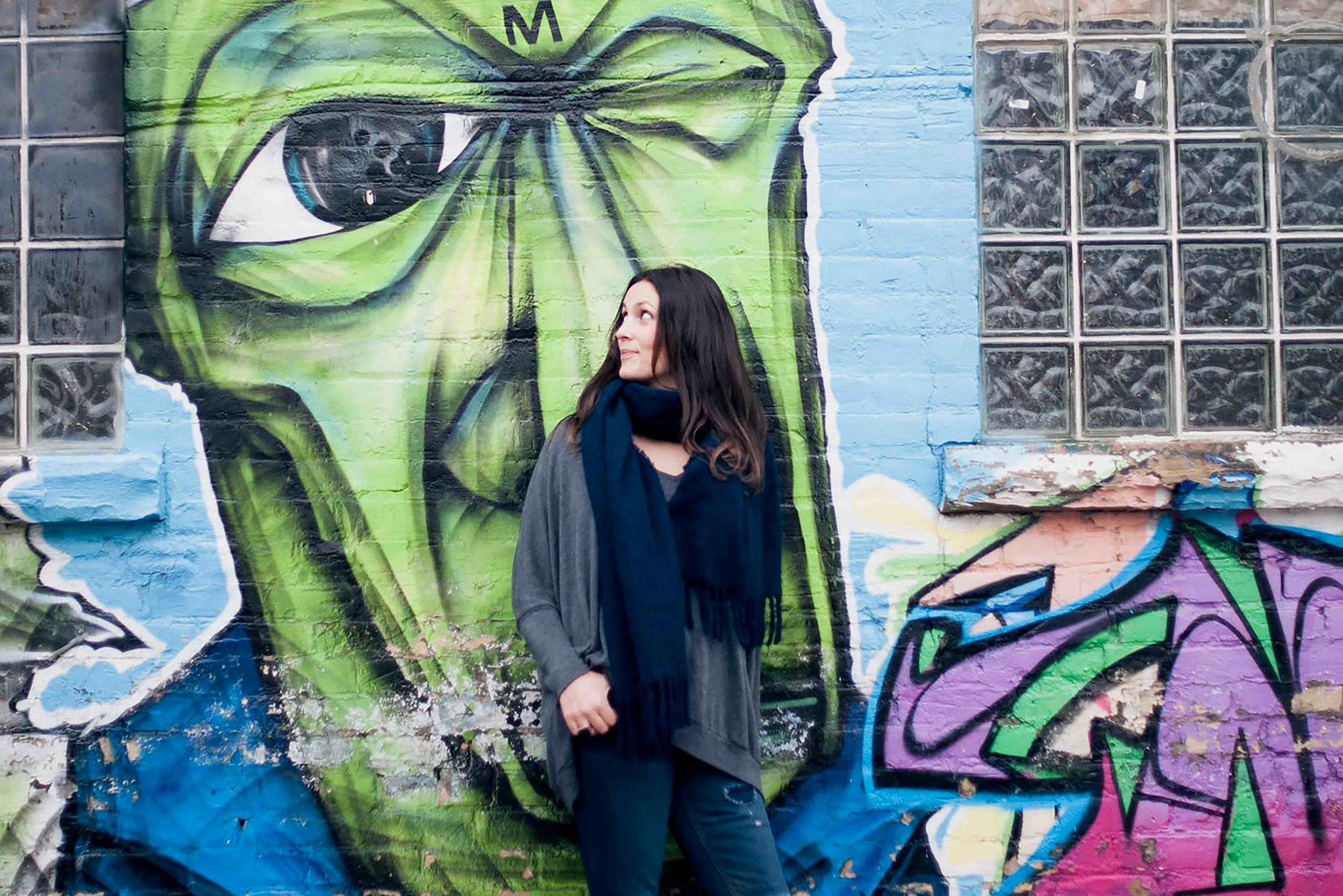 A woman stands against a graffitied brick wall. Behind her is a green face with a large eye, she looks to the side at the eye.