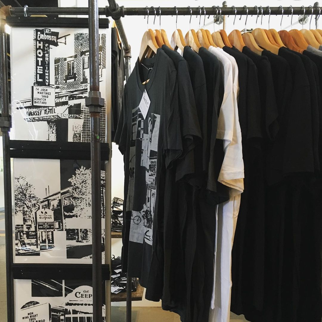 A rack of t-shirts with Me & C designs on them and three black and white prints to the left.