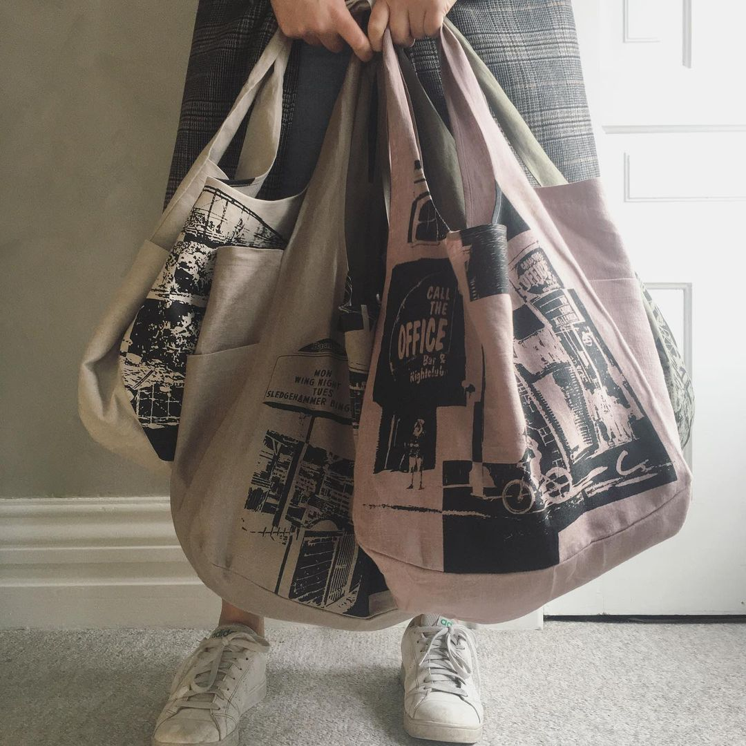 A person holds three totes in front of their legs. The totes are screenprinted by Me & C. and feature three London, On images, including Call the Office.
