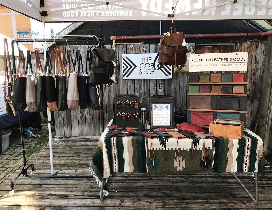 A market booth set up by the COB Shop featuring leather backpacks hanging, leather keychains, a wallet display and a hanging rack full of totes.