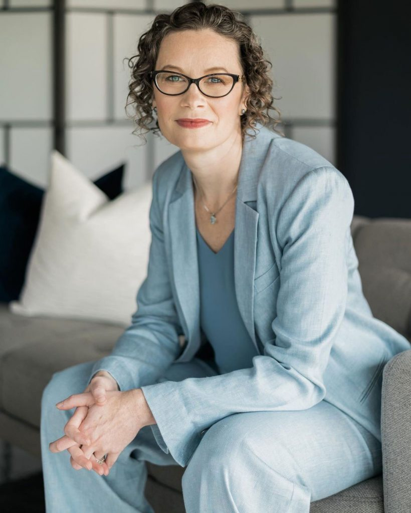 A woman with glasses and dusty rose lipstick wearing a light blue suit