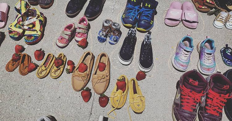Shoes are lined up with strawberries offered on top in remembrance of the lives lost in residential schools in Canada