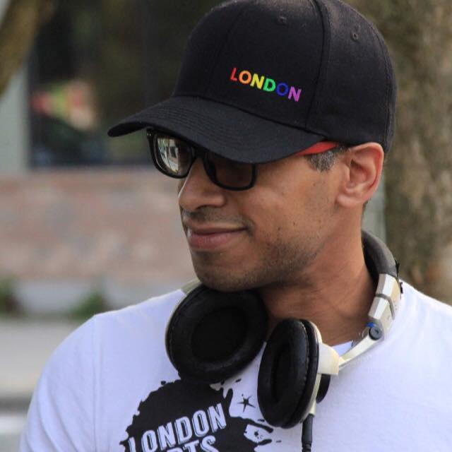 DJ Kevin Evans smiles and looks to the side, wearing a baseball cap and a pair of headphones.