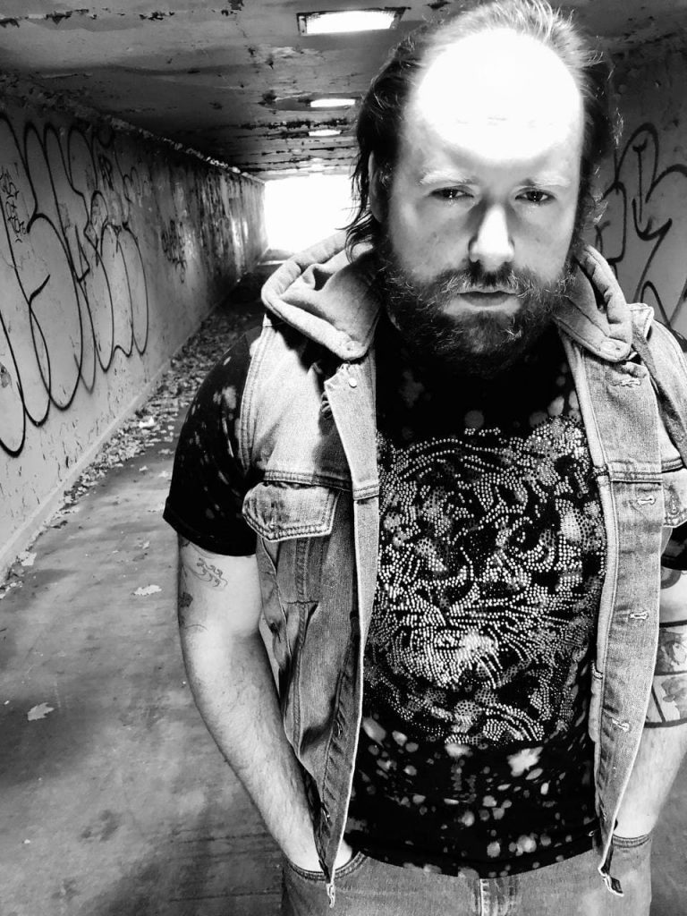Rapper Strange Breed is standing in a tunnel, looking intensely at the camera.