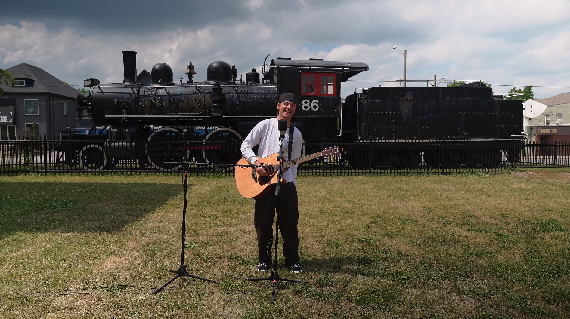 A man in a white shirt and black pants holds a guitar in front of a large black steam engine.