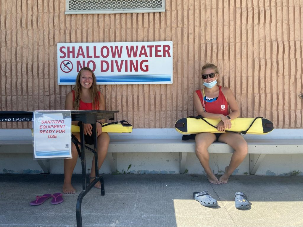Two female lifegaurds are sitting on a bench and taking a break at Gibbons Pool.