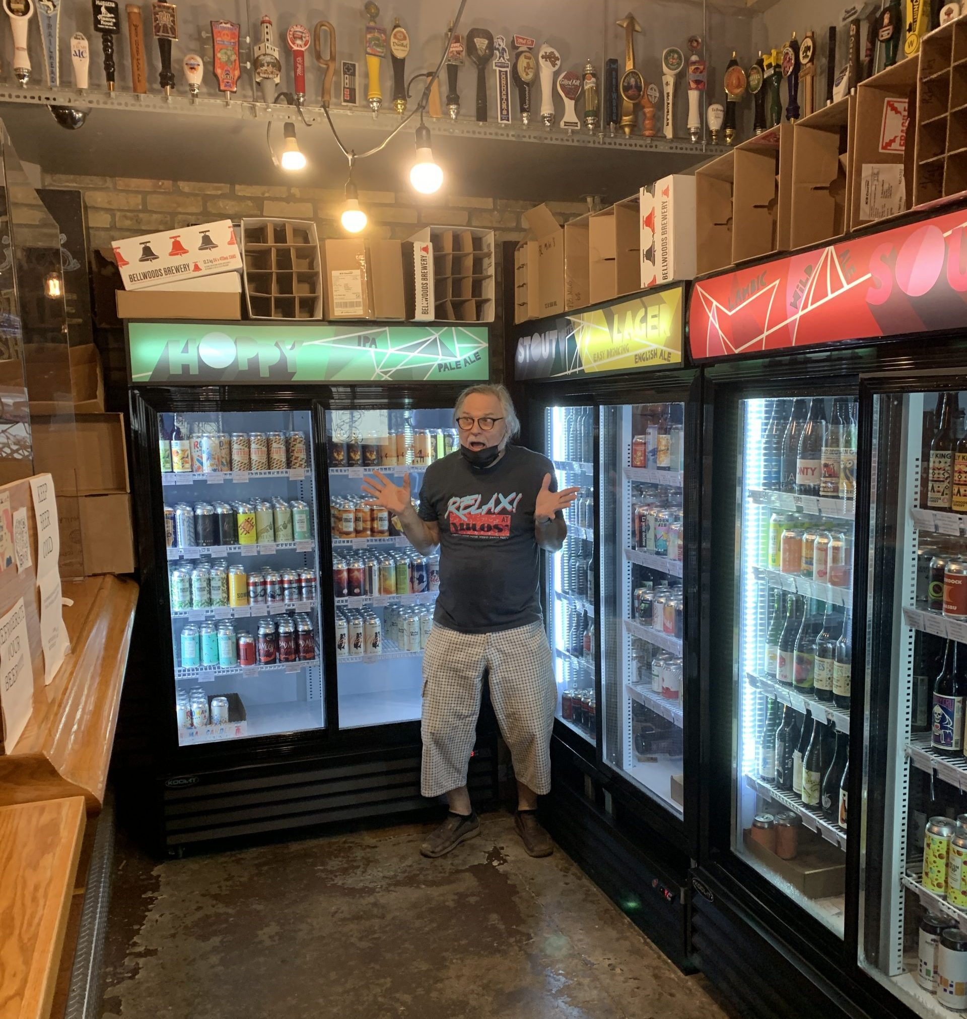 Milos stands in front of his extensive selection of take-home beer.