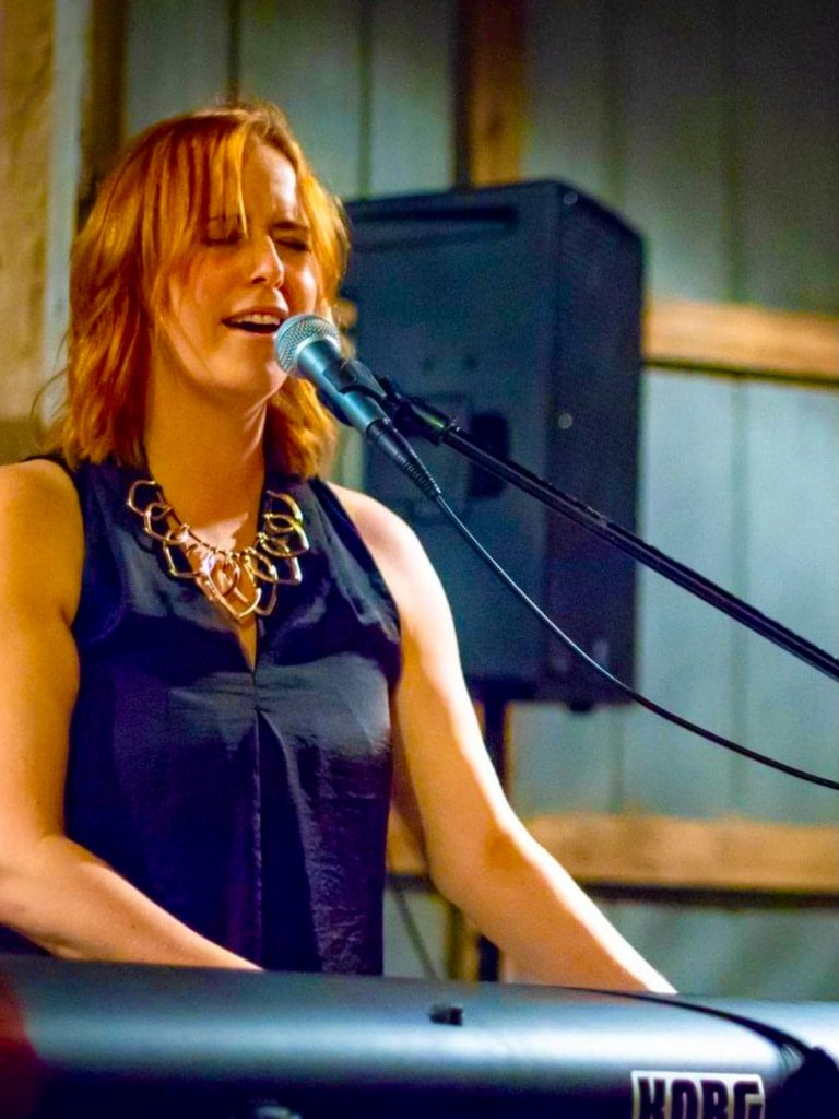 Musician Kay Howl is standing at a keyboard and singing.