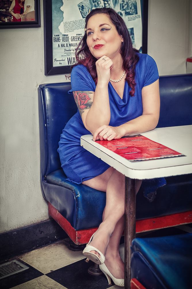 Musician Lori Girard is sitting at a diner table and looking to the left, smiling.
