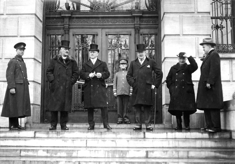 a black and white image of men in top hats standing in front of an open door