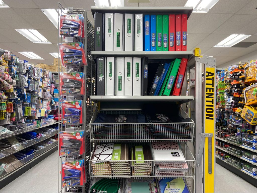 A shelf of binders and notebooks inside of a retail store.