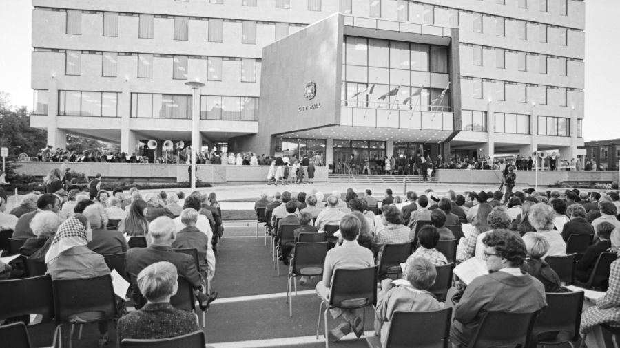 a black and white photo of people sitting in chairs with their backs to the camera, looking at a large building.
