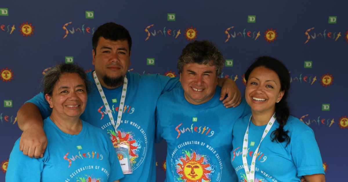 A group of four people in blue Sunfest shirts post in front of a Sunfest sign.