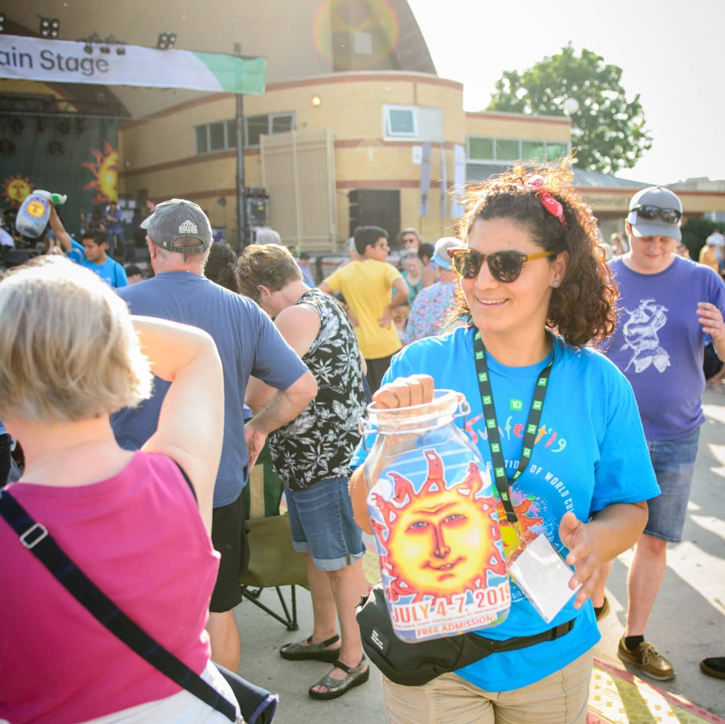 A owman in sunglasses and a ponytail wearing a blue Sunfest shirt holds out a donation container in a crowd.